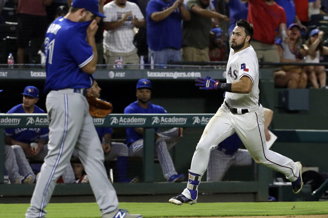 Toronto Blue Jays relief pitcher Joe Biagini walks back to the mound as Texas Rangers' Joey Gallo sprints home after hitting an inside-the-park home run during the fifth inning of a baseball game, ...