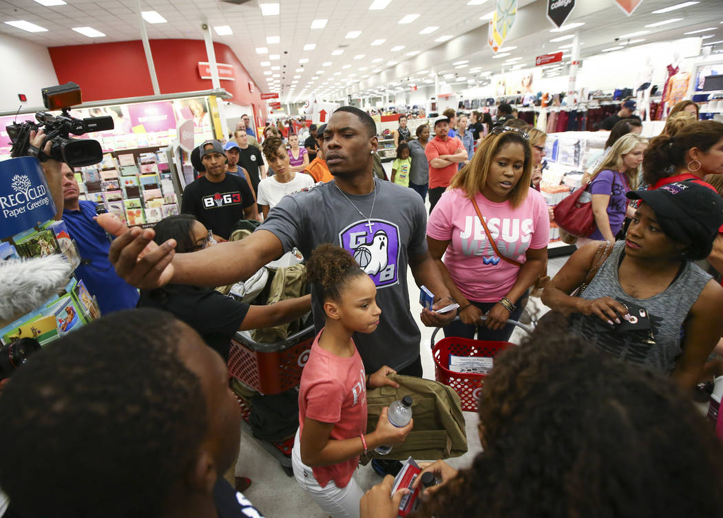 Former UNLV and NBA player Marcus Banks, now a player in the Big 3 basketball league, center left, looks to hand out gift cards during an event held by the Nevada Partnership for Homeless Youth an ...