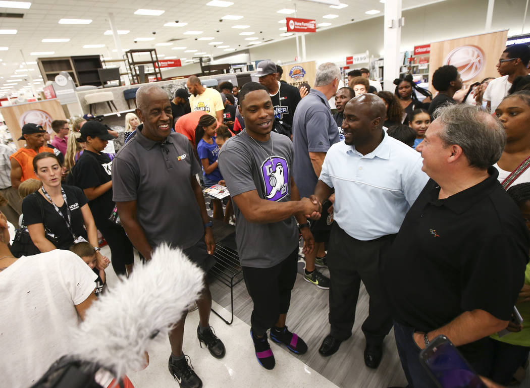 Former UNLV and NBA player Marcus Banks, now a player in the Big 3 basketball league, center, greets Las Vegas City Councilman Ricki Barlow during an event held by the Nevada Partnership for Homel ...