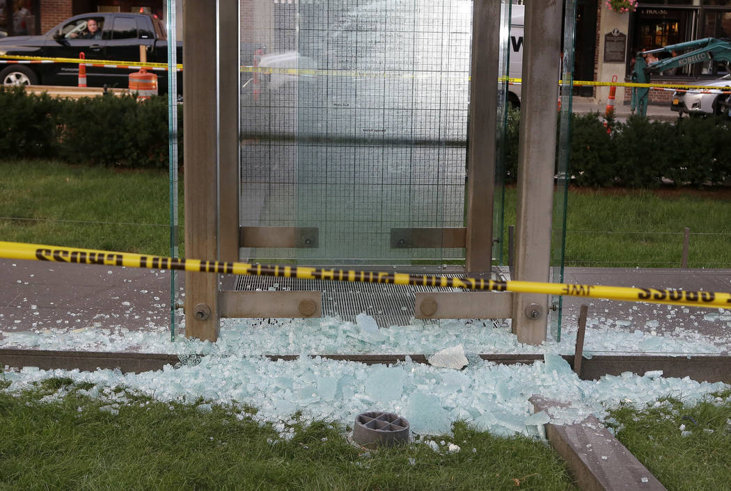 Broken glass lies on the ground near police tape at the New England Holocaust Memorial, Monday, Aug. 14, 2017, in Boston. Police say a person is in custody for allegedly vandalizing the memorial.  ...