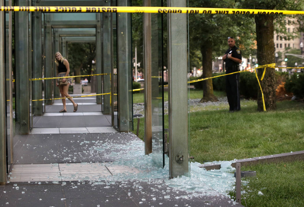 A passerby, left, and a law enforcement official, right, stand near broken glass at the New England Holocaust Memorial on Monday, Aug. 14, 2017, in Boston. Police say a person is in custody for al ...