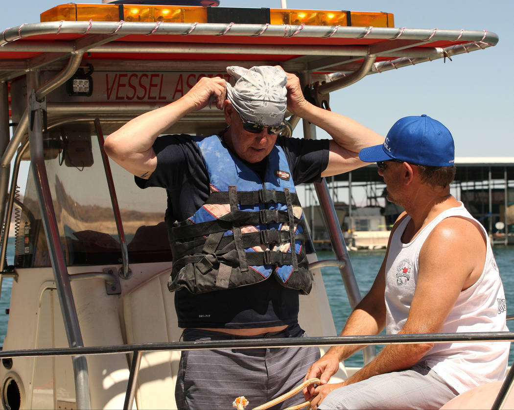 Jim Thompson, left, ties on his bandana before he and Paul Blaylock set out from the Lake Mead Marina to tow boats that may be stranded on the lake, Tuesday, Aug. 15, 2017. Gabriella Benavidez Las ...