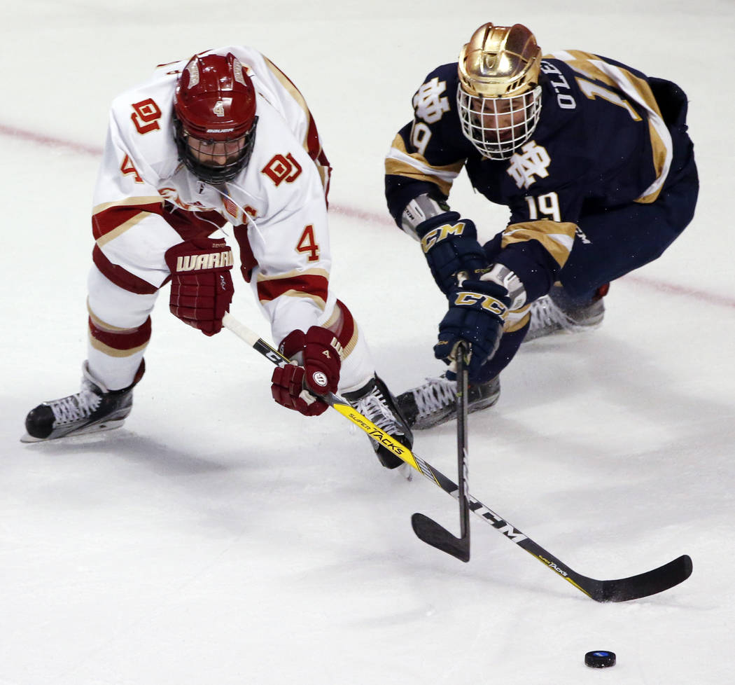 Denver's Will Butcher, left, and Notre Dame's Mike O' Leary vie for the puck during the first period of an NCAA Frozen Four men's college hockey semifinal, Thursday, April 6, 2017, in Chicago. (AP ...