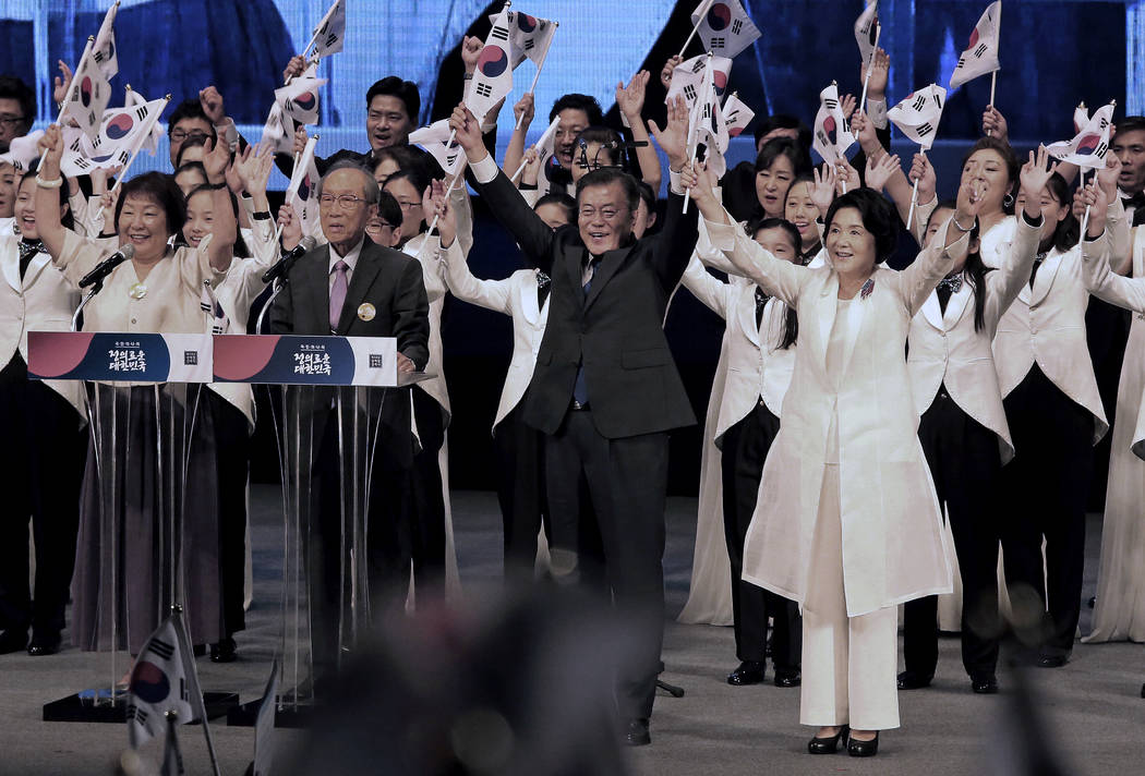 South Korean President Moon Jae-in, center, gives three cheers for his country during a ceremony to celebrate Korean Liberation Day, at Seong Cultural Center in Seoul, South Korea, Tuesday, Aug. 1 ...