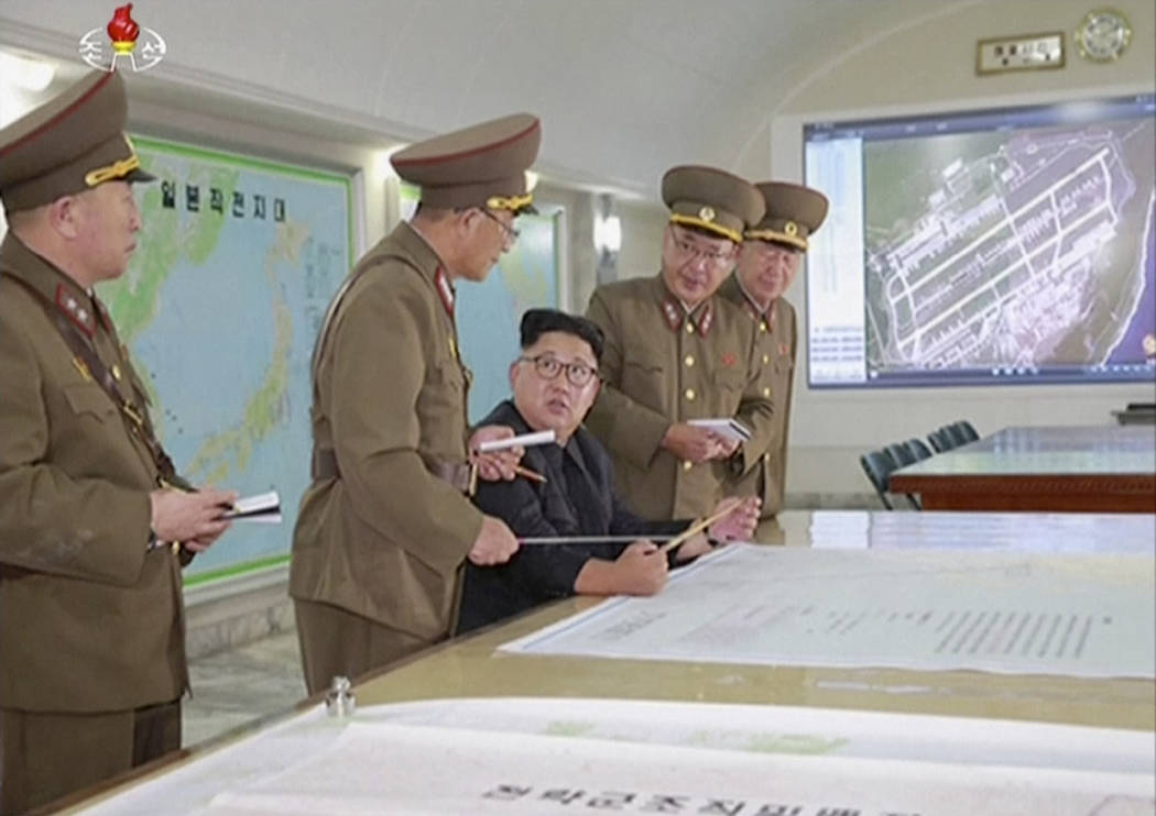 This image made from video of an Aug. 14, 2017, still image broadcast in a news bulletin on Tuesday, Aug. 15, 2017, by North Korea's KRT shows North Korean leader Kim Jong Un receiving a briefing  ...