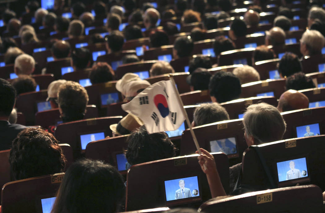 South Korean President Moon Jae-in delivering a speech are seen on small screens during a ceremony to celebrate Korean Liberation Day at Seong Cultural Center in Seoul, South Korea, Tuesday, Aug.  ...