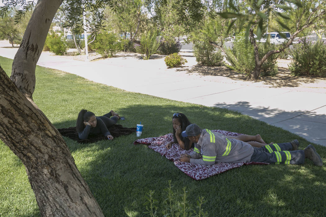 Lara Levi, left, Siatulau Ausage, center, and Michael Roby, right, all from Las Vegas, rest in the shade at Silverado Ranch Park in Las Vegas, Tuesday,Aug. 15, 2017. Gabriella Angotti-Jones Las Ve ...