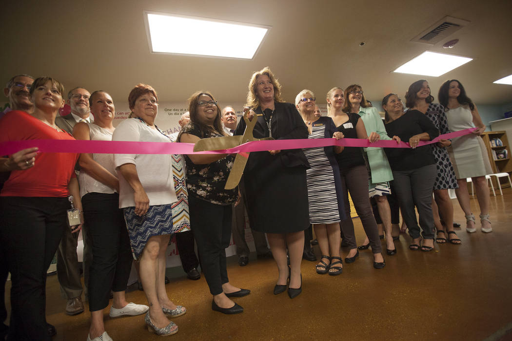 Stacey Lockhart, executive director of The Shade Tree women's shelter, cuts a ribbon at a fundraiser for the shelter on Thursday, Aug. 24, 2017, at The Shade Tree in Las Vegas. The shelter serves  ...