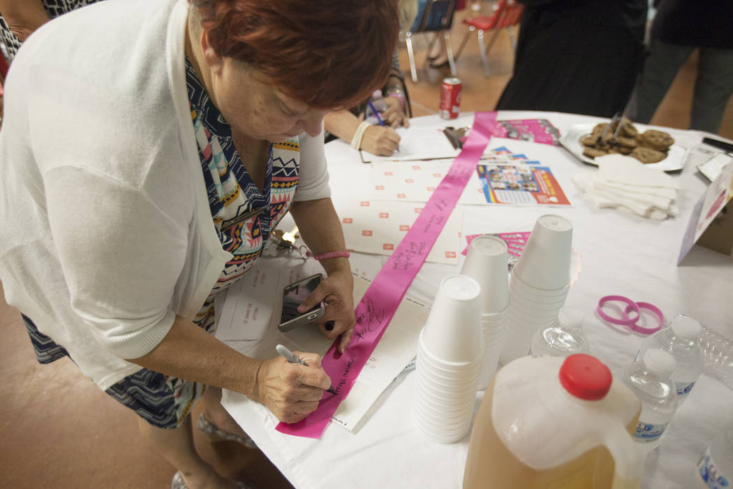 Marian Thomas, volunteer coordinator at The Shade Tree, signs a ribbon with her name on Thursday, Aug. 24, 2017, at The Shade Tree in Las Vegas. The shelter that serves women and children kicked o ...