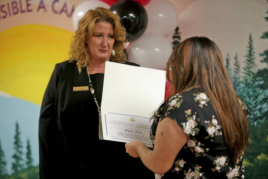 Ashley Garcia, a staff assistant for Rep. Ruben Kihuen, delivers a donation to Stacey Lockhart, executive director of The Shade Tree women's shelter, at a fundraiser on Thursday, Aug. 24, 2017, at ...