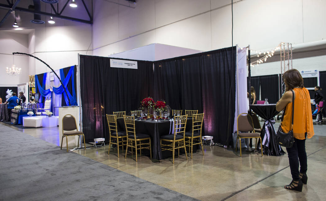 An attendee looks at the DragonRidge Country Club booth during the Bridal Spectacular wedding expo at Cashman Center in Las Vegas on Saturday, Aug. 19, 2017. Chase Stevens Las Vegas Review-Journal ...