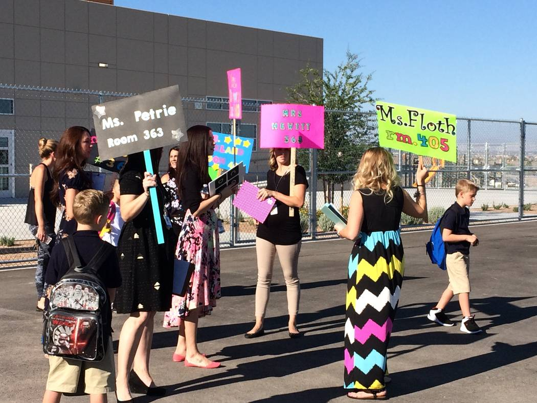 Teachers hold signs with their names Aug.14, 2017,  to alert students where they should line up before heading to their proper spots on the playground. The school was so new the sun shades had not ...