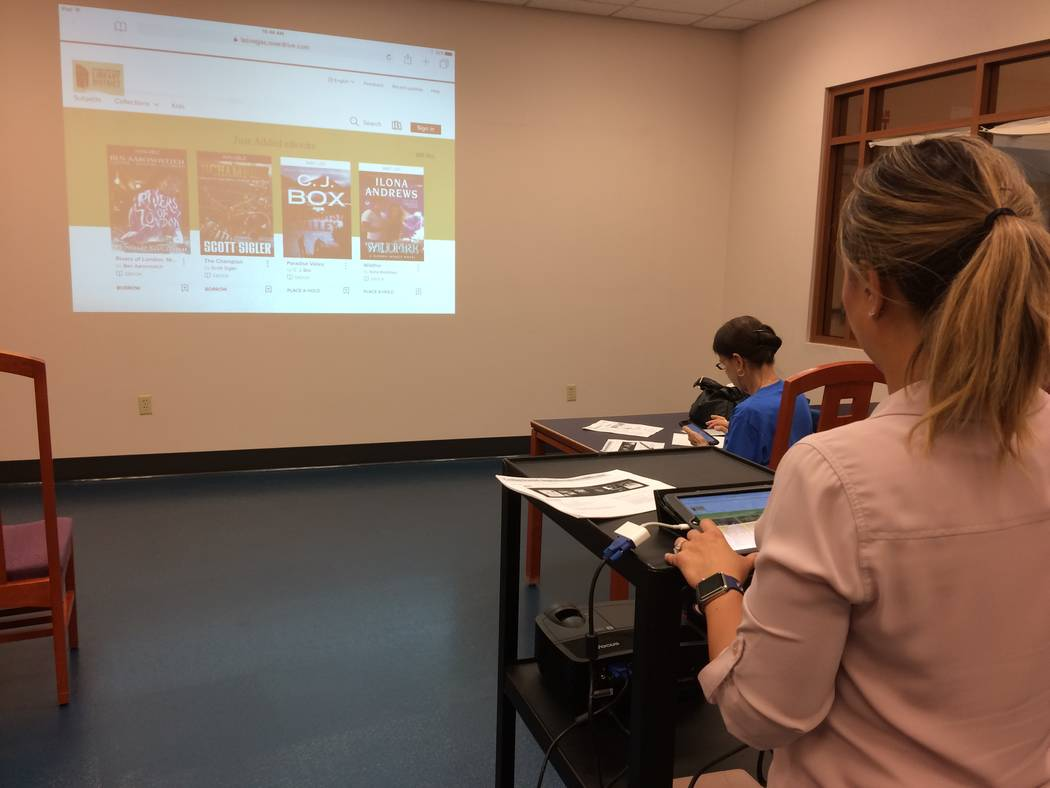 "Maria ""Ria"" Eufemio shows library patrons how to download books, movies, magazines and music July 27, 2017, at Summerlin Library. Eufemio has been giving a class titled Downloading eMedia for  ..."