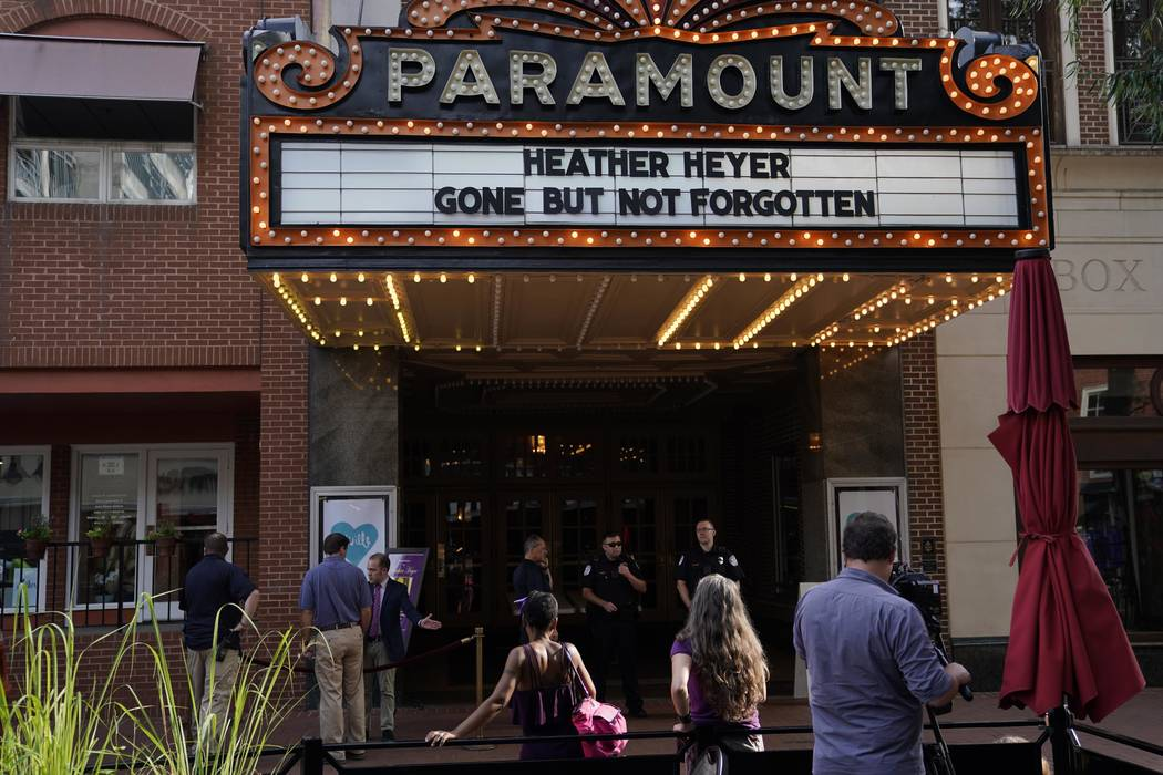 A cameraman stands among mourners and police outside the Paramount Theater prior to a memorial service for car attack victim Heather Heyer in Charlottesville, Virginia, Aug. 16. 2017. (Jonathan Er ...