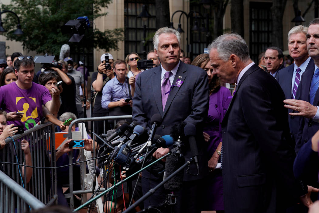 Virginia Governor Terry McAuliffe (C) and U.S. Senator Tim Kaine (D-VA) (L) speak to reporters after a memorial service for car attack victim Heather Heyer at the Paramount Theater in Charlottesvi ...