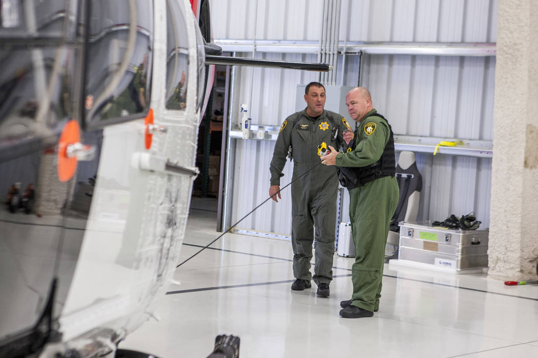 Chief Pilot Steve Morris Jr., center,  and pilot Bryan Woolard prepare the new Las Vegas Metropolitan Police helicopter for flight at the North Las Vegas Airport on Wednesday, Aug. 16, 2017.  Patr ...