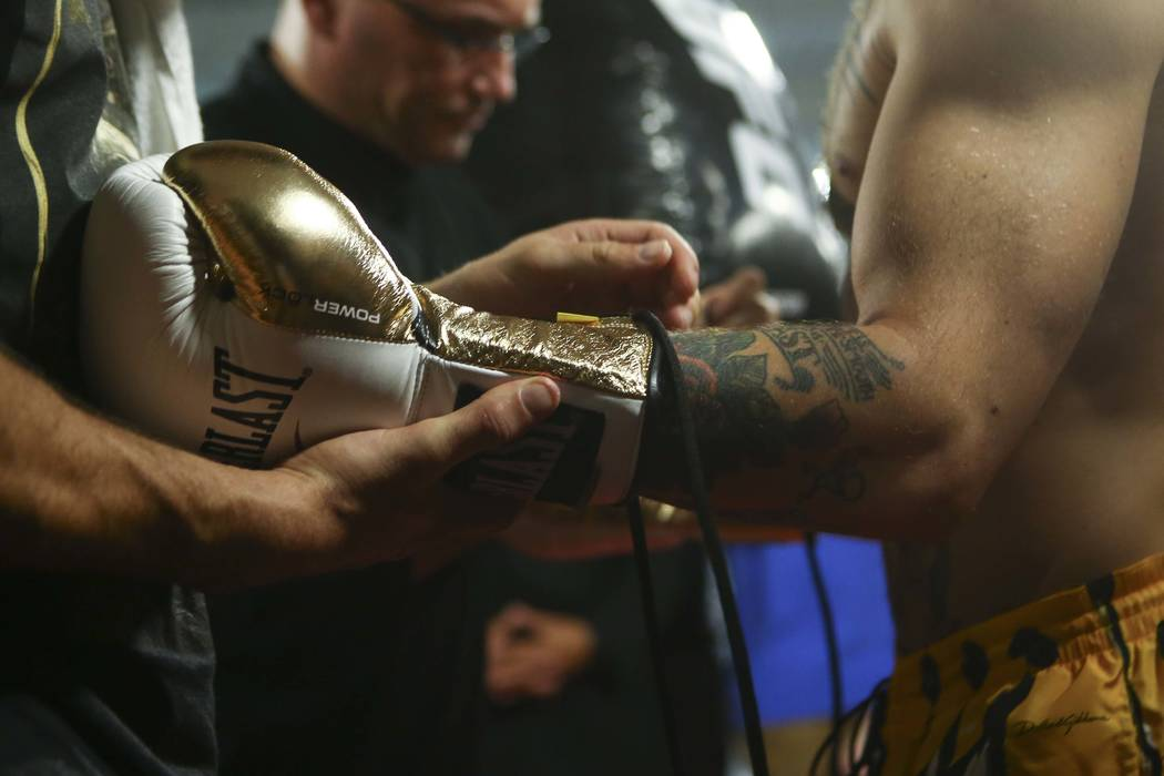 UFC fighter Conor McGregor gets a boxing glove on during a workout ahead of his boxing match against Floyd Mayweather Jr., at the UFC Performance Institute in Las Vegas on Friday, Aug. 11, 2017. ( ...