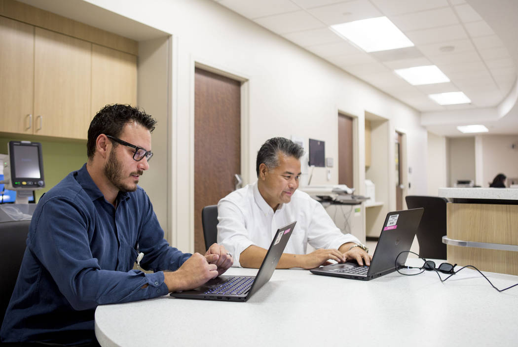 Information Technology specialists Ryan Lagasse, left, and Eugene Imasa work on electronic records at the third of four Las Vegas-area Dignity Health St. Rose Dominican neighborhood hospitals, at  ...