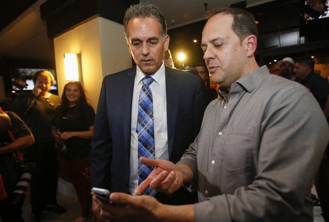Republican Congressional District 3 candidate Danny Tarkanian, left, looks at campaign results with Jamie Fisfis during his election night gathering at Born and Raised in Las Vegas on Tuesday, Jun ...
