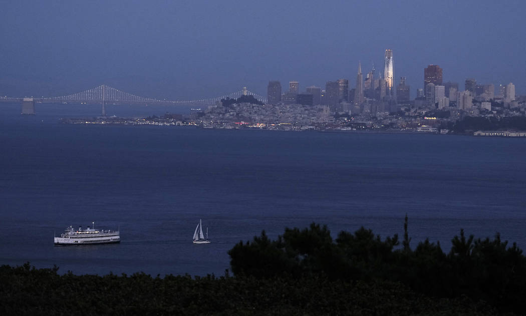 In this photo taken Saturday, July 22, 2107, the setting sun is reflected on the Salesforce Tower in the San Francisco skyline in this view from Sausalito, Calif. Construction crews are putting th ...
