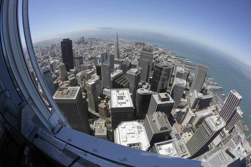 In this photo taken Tuesday, July 11, 2017, the Transamerica Pyramid and Golden Gate Bridge at left are seen below from the top of the Salesforce Tower in San Francisco. Construction crews are put ...