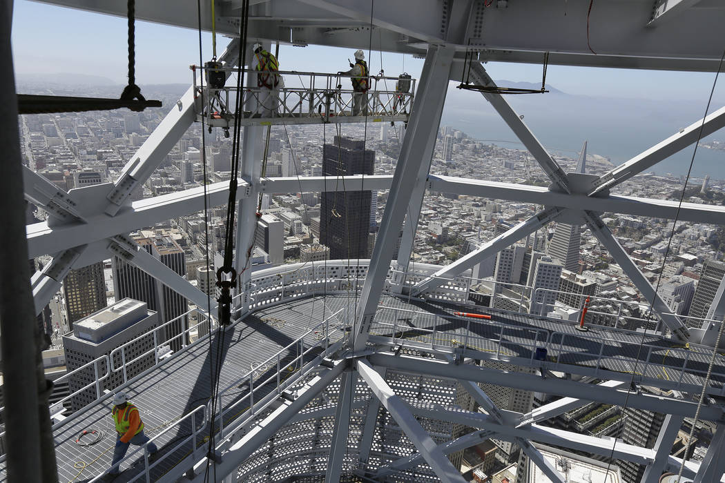 This photo taken Tuesday, July 11, 2017 shows construction workers just below the top of the Salesforce Tower in San Francisco.  Construction crews are putting the finishing touches on San Francis ...