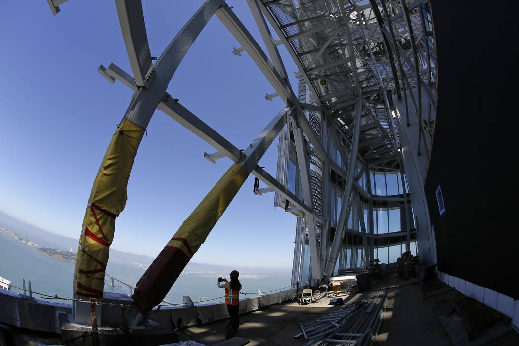 In this photo taken Tuesday, July 11, 2017, a woman looks out toward the San Francisco-Oakland Bay Bridge from just below the top of the Salesforce Tower in San Francisco. Construction crews are p ...