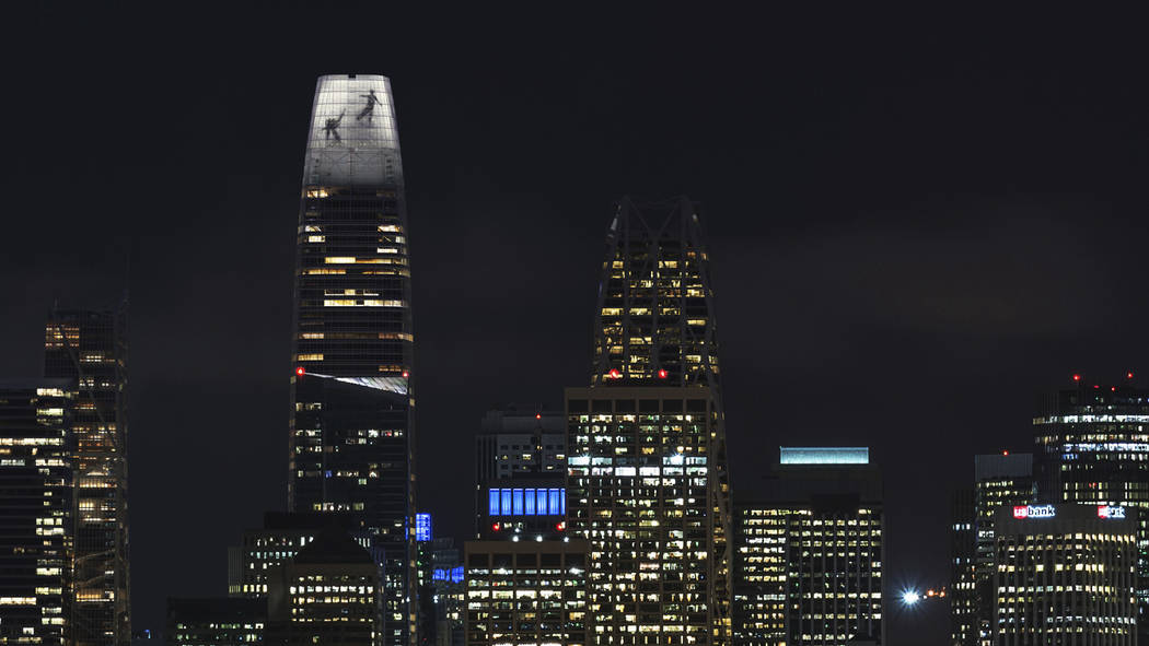 In this image depiction provided by LED artist Jim Campbell, the outline of two dancers captured mid-motion is displayed on the nine-story electronic art installation atop the $1.1 billion Salesfo ...