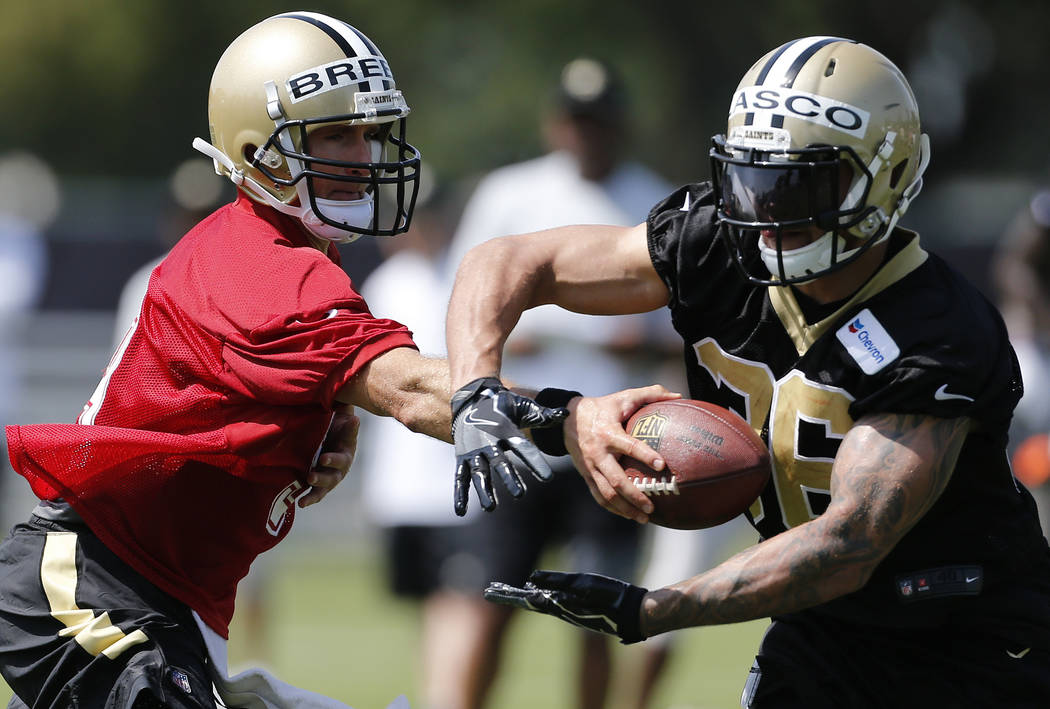 New Orleans Saints quarterback Drew Brees (9) hands the ball to running back Daniel Lasco (36) during NFL football training camp in Metairie, La., Friday, July 28, 2017. (AP Photo/Jonathan Bachman)