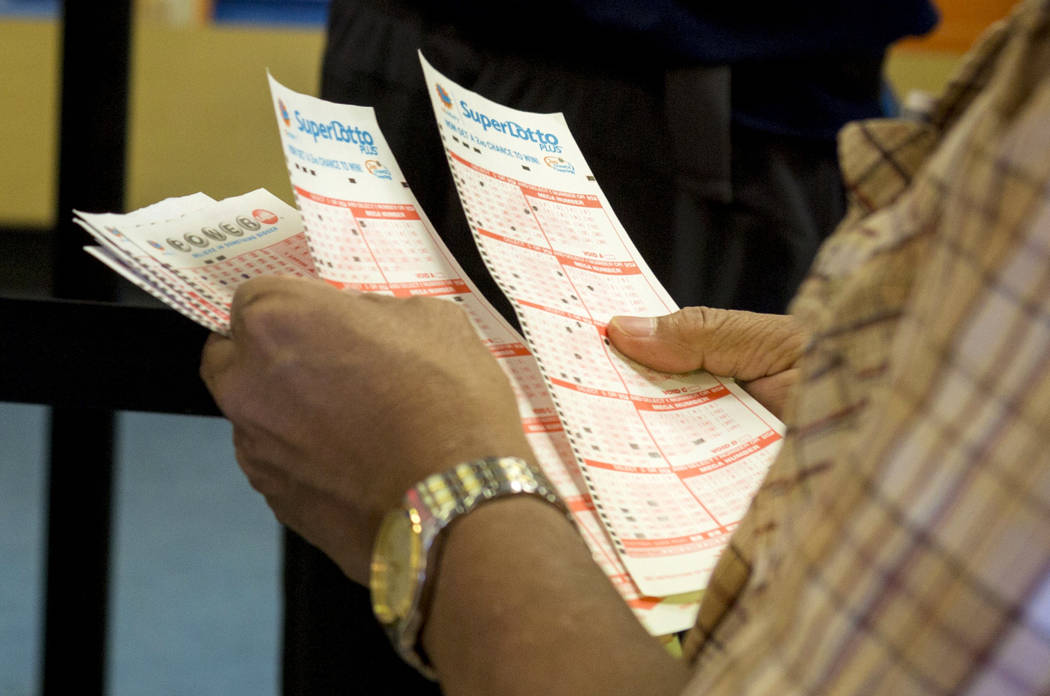 A man looks over his numbers on his Powerball tickets at the Primm Valley Lotto Store, Wednesday, Aug. 16, 2017. Elizabeth Brumley Las Vegas Review-Journal