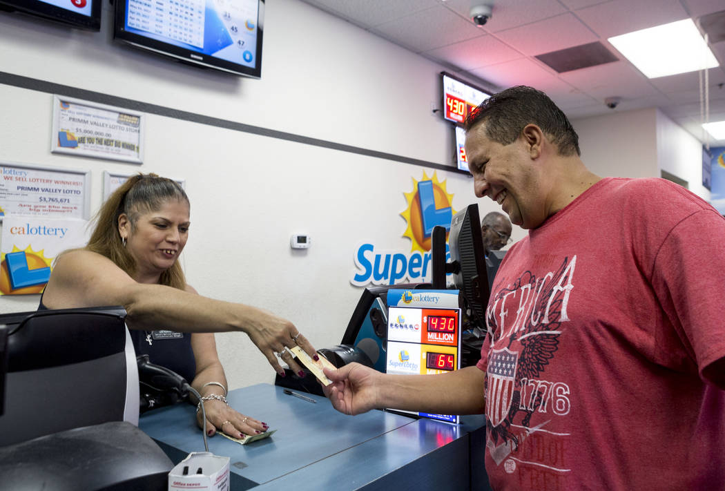Benjamin Mondher, right, purchases Powerball tickets from Lotto Manager Barbara Martinez-Humphrey, left, at the Primm Valley Lotto Store, Wednesday, Aug. 16, 2017. Elizabeth Brumley Las Vegas Revi ...