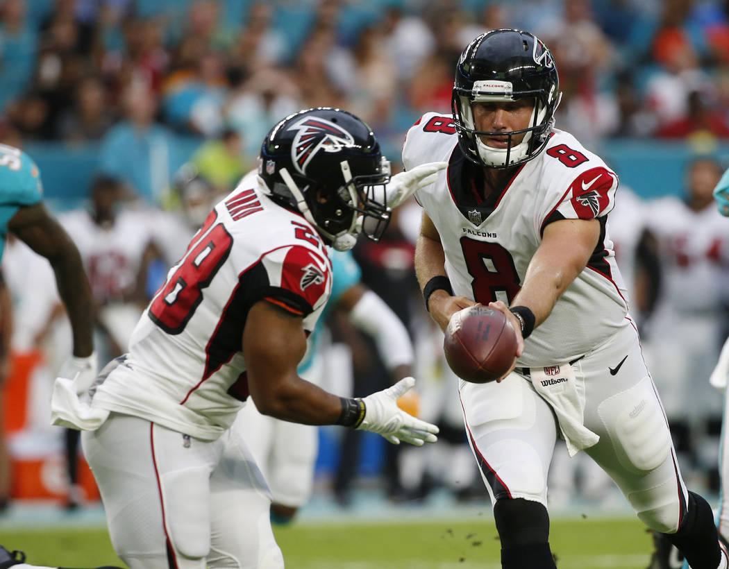 Atlanta Falcons quarterback Matt Schaub (8) hands the ball to running back Terron Ward (28), during the first half of an NFL preseason football game against the Miami Dolphins, Thursday, Aug. 10,  ...