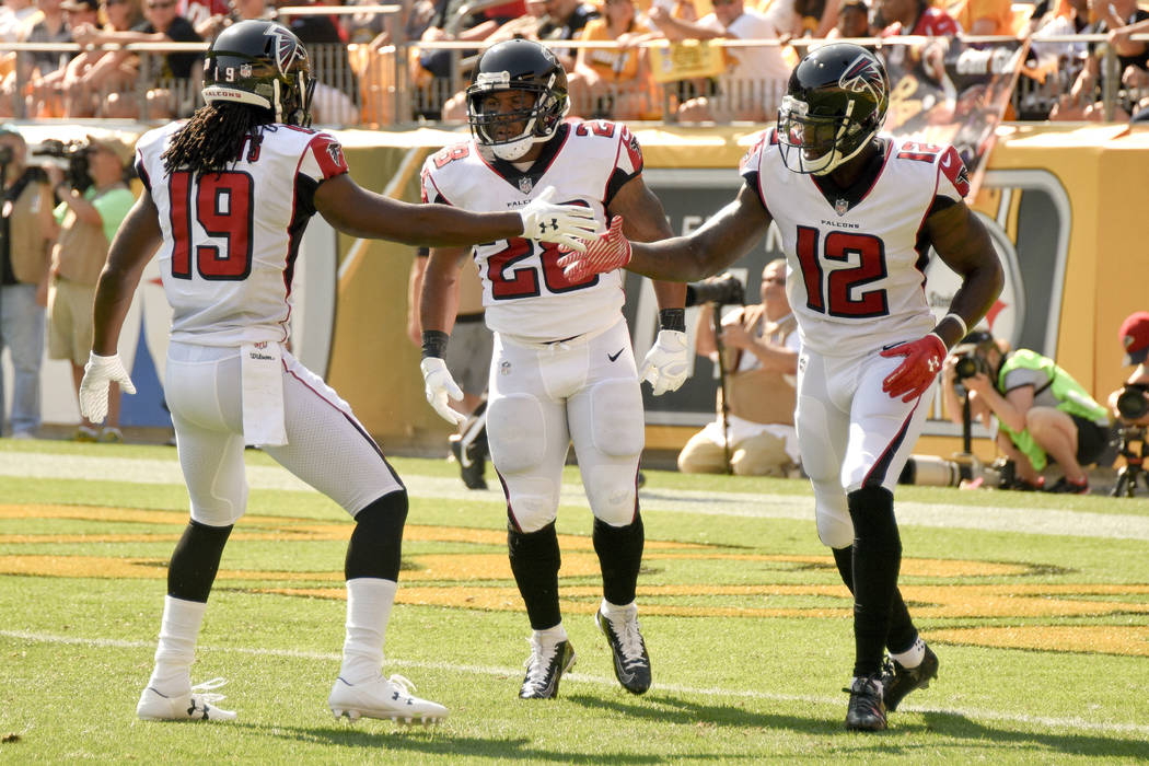 Atlanta Falcons running back Terron Ward (28), left, is congratulated by wide receivers Mohamed Sanu (12) and Andre Roberts (19) after scoring a touchdown in the first quarter of an NFL preseason  ...