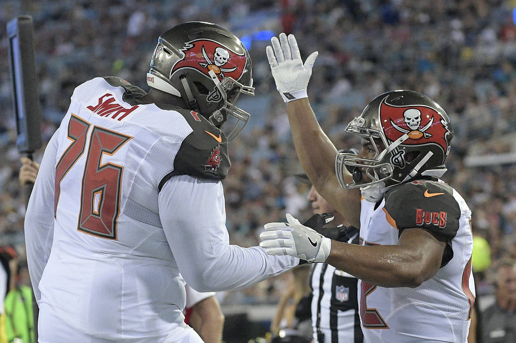 Tampa Bay Buccaneers running back Doug Martin, right, celebrates after his touchdown run against the Jacksonville Jaguars with teammate tackle Donovan Smith (76) during the first half of an NFL pr ...