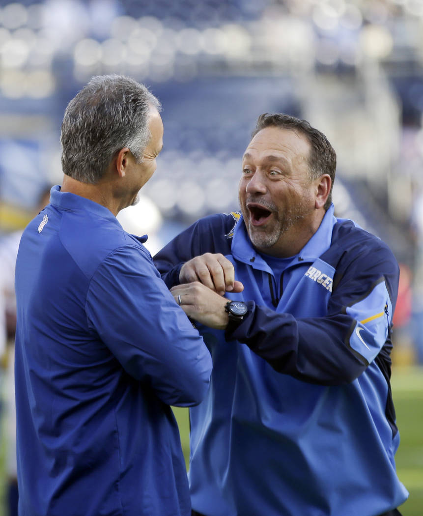 Indianapolis Colts head coach Chuck Pagano , left, jokes with his brother, and San Diego Chargers defensive coordinator John Pagano, right, before an NFL football game Monday, Oct. 14, 2013, in Sa ...