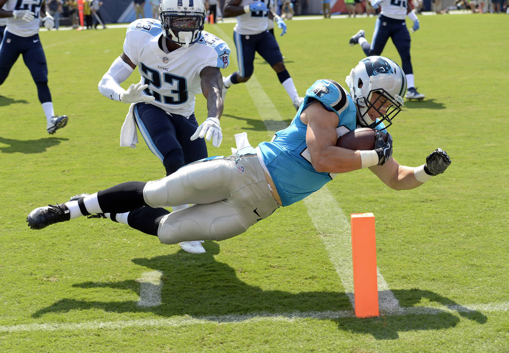 This Aug. 19, 2017, file photo shows Carolina Panthers running back Christian McCaffrey diving into the end zone for a touchdown on a 17-year run ahead of Tennessee Titans cornerback Brice McCain  ...