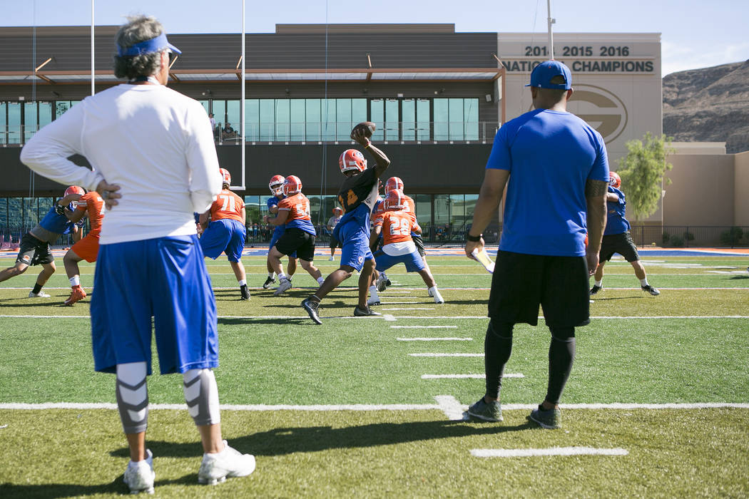 Bishop Gorman quarterback Dorian Thompson Robinson, center, passes the ball during practice with his team at Fertitta Field at Bishop Gorman High School Monday, Aug. 21, 2017, in Las Vegas. Bridge ...