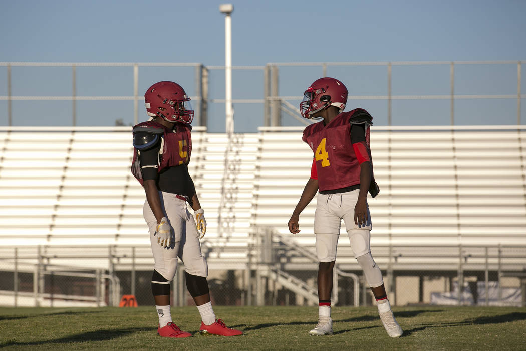 Del Sol senior Taariq Flowers, left, talks with his brother and sophomore teammate Maalik Flowers during a three-team scrimmage at Del Sol High School on Friday, Aug. 18, 2017, in Las Vegas. Bridg ...
