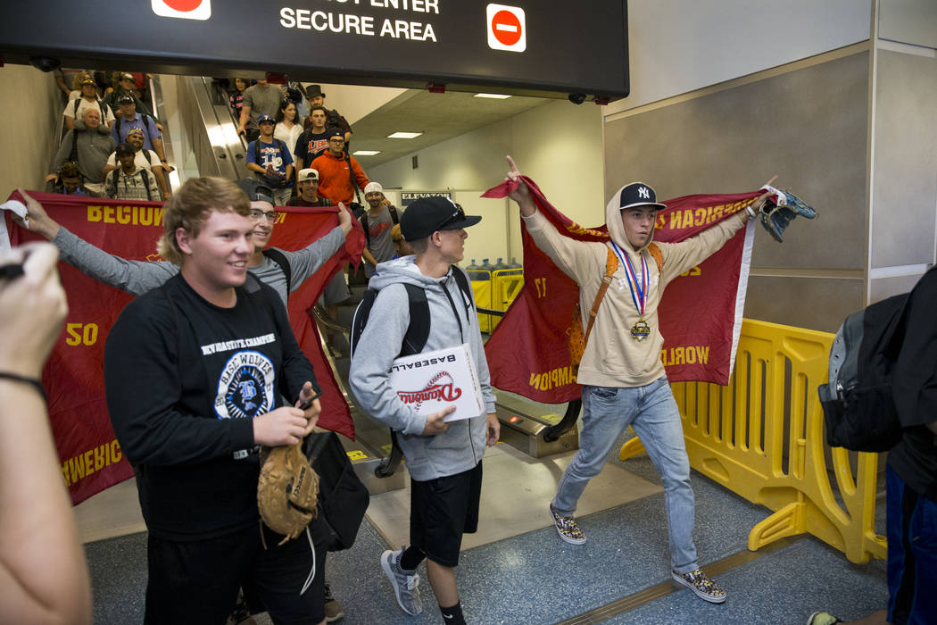 Southern Nevada Blue Sox baseball players from left, Jack Wold, coach Tyler Baker, and John-Howard Bobo, arrive with their team at McCarran International Airport in Las Vegas, on Wednesday, Aug. 1 ...