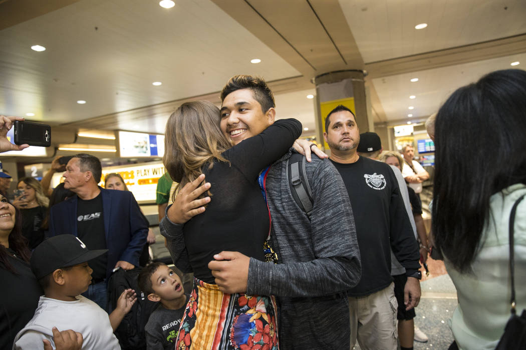 Basic High School students Kianna Jordan, left, 15, hugs Kai Symonds, 17, during his baseball team Southern Nevada Blue Sox arrival to McCarran International Airport after their victory in the Ame ...
