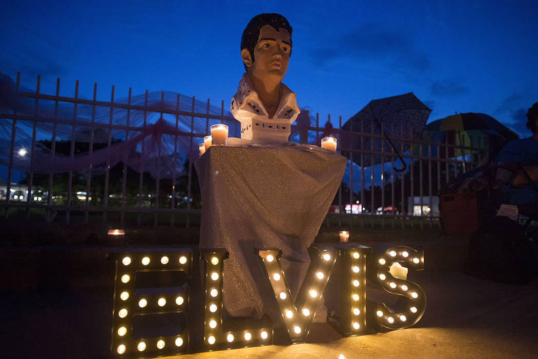 A street memorial is lit during a candlelight vigil for Elvis Presley in front of Graceland, Presley's Memphis home, on Tuesday, Aug. 15, 2017, in Memphis, Tenn. Fans from around the world are at  ...