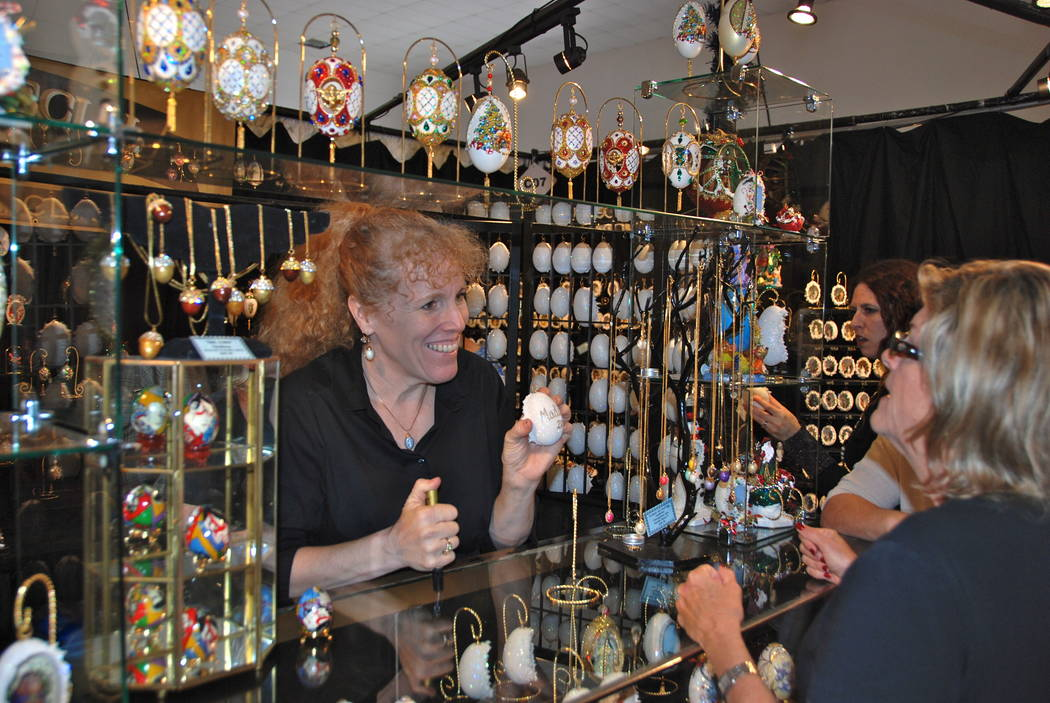 An exhibitor shows a potential customer some of her wares at Harvest Fest. (Photo by MAA4 Events)