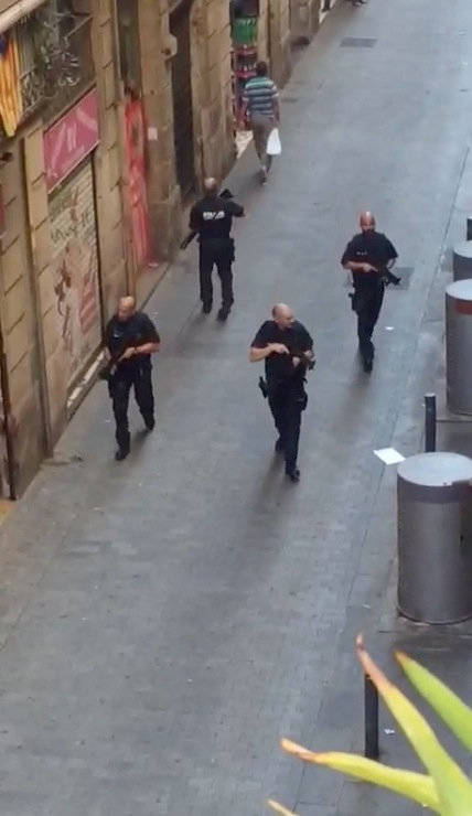 Armed police officers patrol an empty street, after a van crashed into pedestrians near the Las Ramblas avenue in central Barcelona, Spain August 17, 2017, in this still image from a video obtaine ...