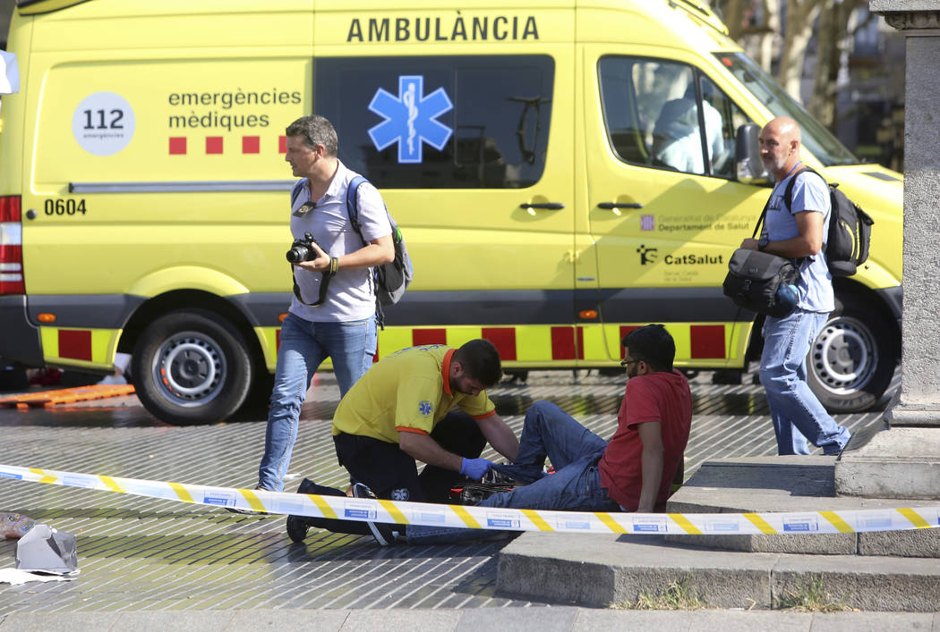 An injured person is treated in Barcelona, Spain, Thursday, Aug. 17, 2017 after a white van jumped the sidewalk in the historic Las Ramblas district, crashing into a summer crowd of residents and  ...