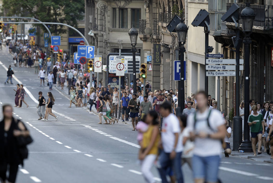 People walk down a main street in Barcelona, Spain, Thursday, Aug. 17, 2017. Police in Barcelona say a white van has mounted a sidewalk, struck several people in the city's Las Ramblas district. ( ...