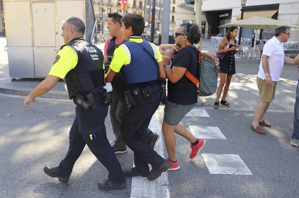 An injured person is carried in Barcelona, Spain, Thursday, Aug. 17, 2017 after a white van jumped the sidewalk in the historic Las Ramblas district, crashing into a summer crowd of residents and  ...