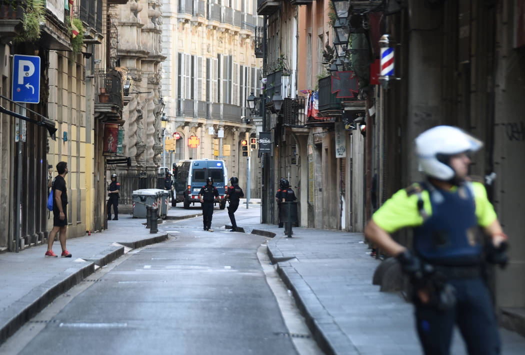 Police secure the area close to the scene after a white van jumped the sidewalk in the historic Las Ramblas district of Barcelona, Spain, crashing into a summer crowd of residents and tourists Thu ...