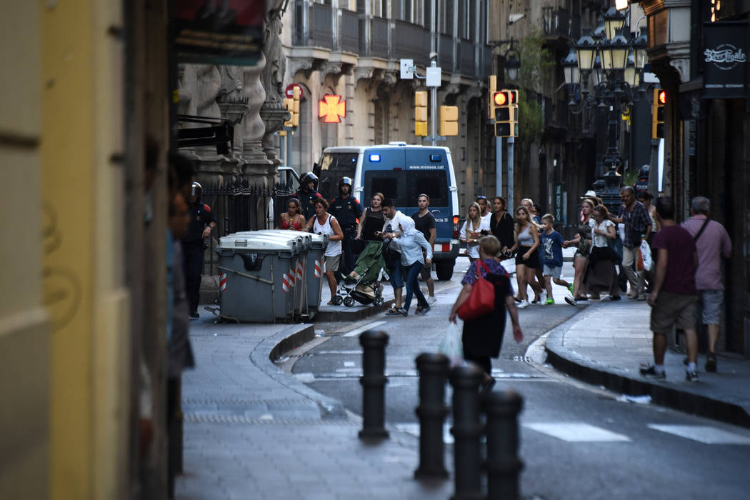 People flee the scene in Barcelona, Spain, Thursday, Aug. 17, 2017, as police officers patrols after a white van jumped the sidewalk in the historic Las Ramblas district, crashing into a summer cr ...