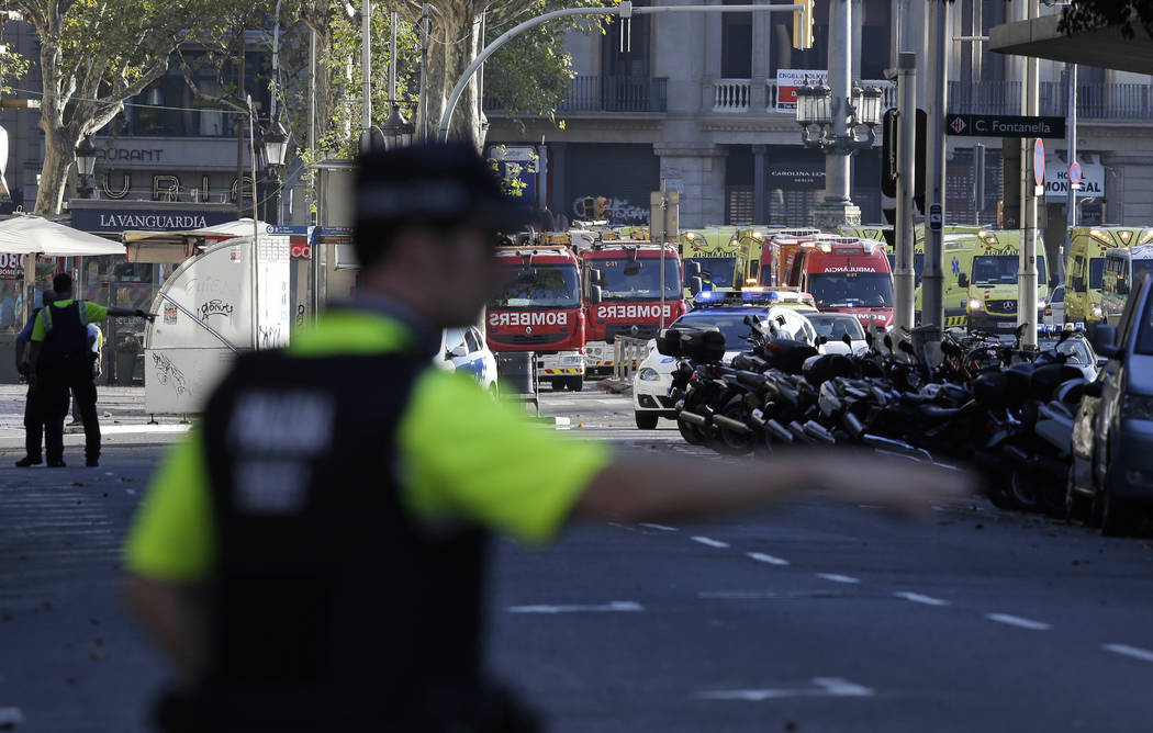 A police officer gestures as he blocks a street in Barcelona, Spain, Thursday, Aug. 17, 2017. Police in the northern Spanish city of Barcelona say a white van has jumped the sidewalk in the city's ...