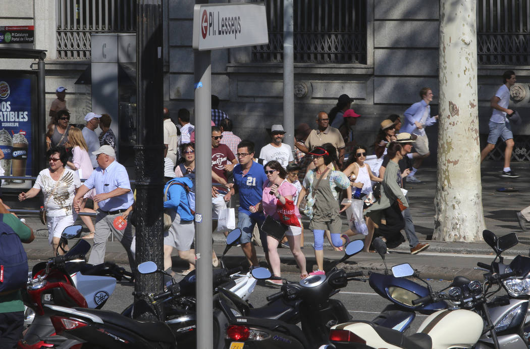 People flee the scene in Barcelona, Spain, Thursday, Aug. 17, 2017 after a white van jumped the sidewalk in the historic Las Ramblas district, crashing into a summer crowd of residents and tourist ...